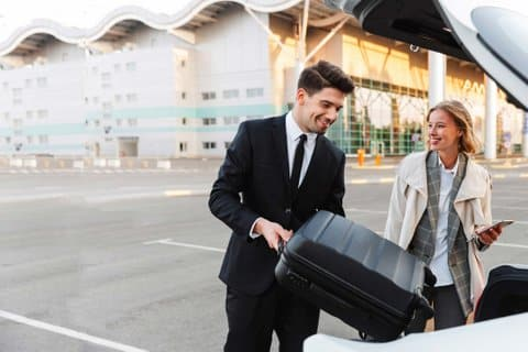 private chauffeur pulling luggage from his car